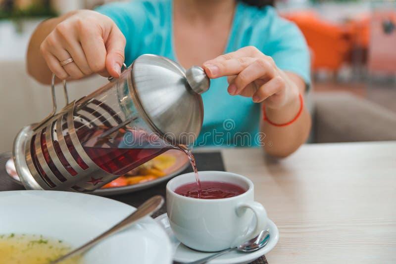 Las manos de la mujer se cierran encima de té de colada de la fruta de la caldera fotografía de archivo libre de regalías