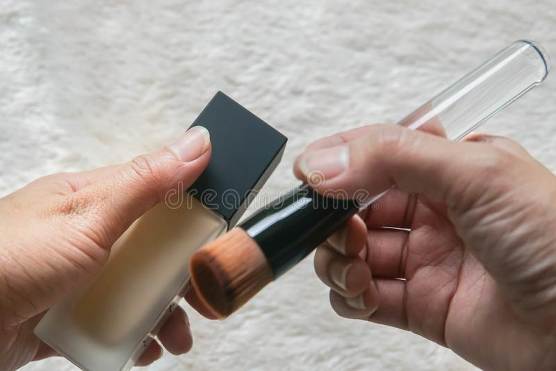 Las manos de la mujer se sostienen componen el sistema de cepillo con la fundación líquida para que el maquillaje trabaje imagen de archivo libre de regalías