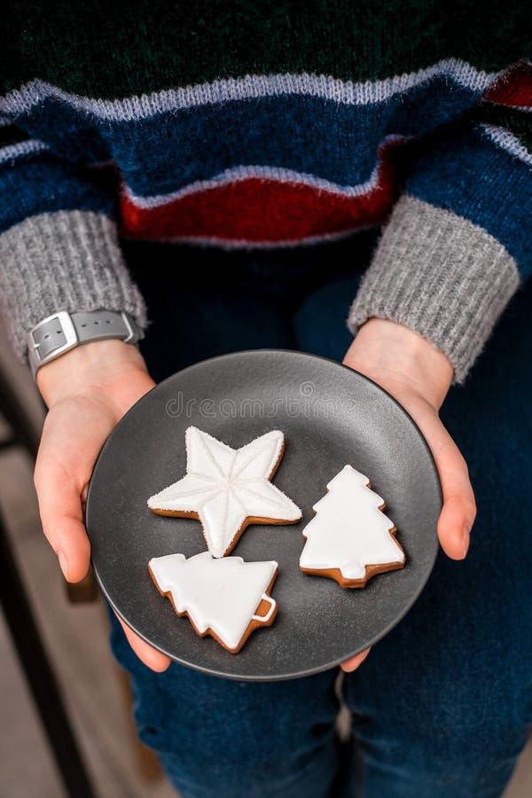 Las manos de la mujer sostienen la placa con las galletas de la Navidad imágenes de archivo libres de regalías