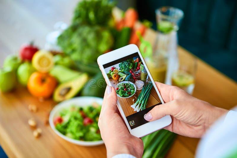 Las manos de la mujer toman la foto de la comida del smartphone de la ensalada de las verduras con los tomates y las frutas Fotog fotografía de archivo libre de regalías