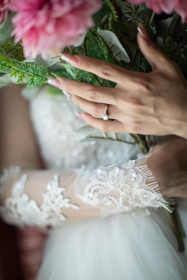 Las manos de la novia con las flores Ramo en las manos de la novia, mujer que consigue lista antes de ceremonia de boda fotografía de archivo libre de regalías