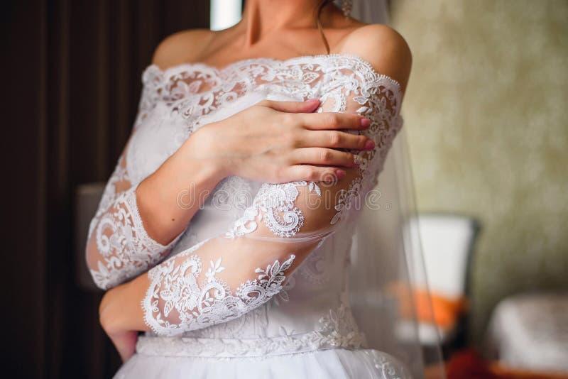 Las manos de la novia con una boda manicure en clavos foto de archivo libre de regalías