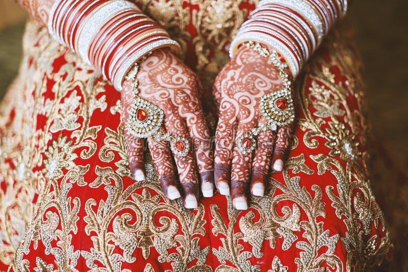 Las manos de la novia india con el tatuaje de la alheña del menhdi y del manojo de brazaletes en su muñeca, primer del brillo imagenes de archivo