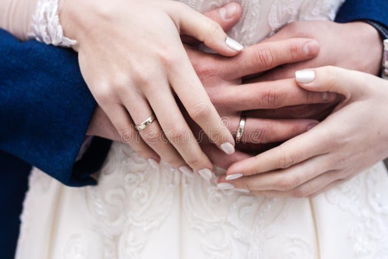 Las manos de la novia y del novio con los anillos se cierran para arriba imagen de archivo libre de regalías