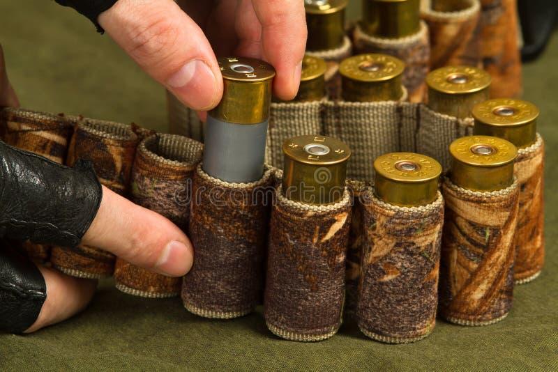 Las manos de la pistola llenan una bandolera de la munición imagenes de archivo