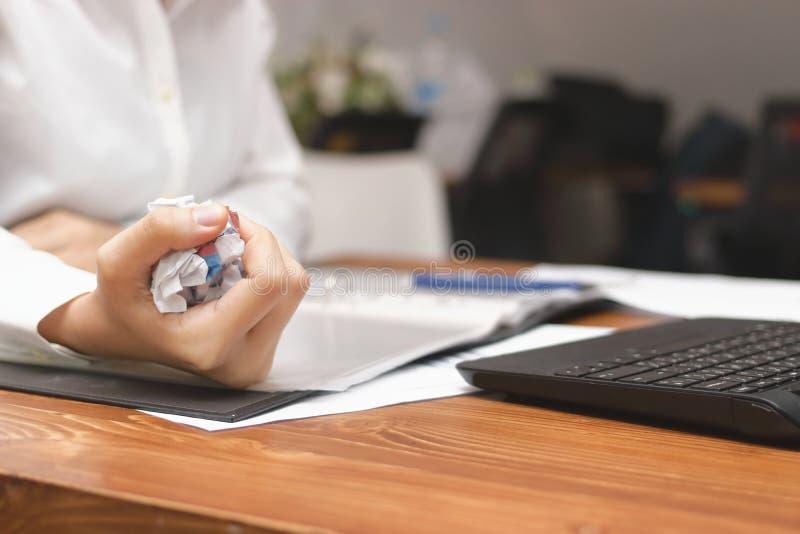 Las manos de la tenencia de la empresaria arrugaron el documento sobre lugar de trabajo en oficina Fracaso y concepto cansado del imagenes de archivo
