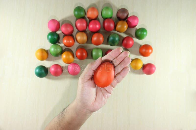 Las manos de la visión superior del hombre joven que sostienen los huevos de Pascua coloridos en el mármol rematan el fondo foto de archivo