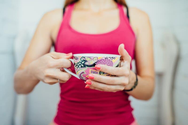 Las manos de las mujeres que sostienen una taza colorida de té imagenes de archivo