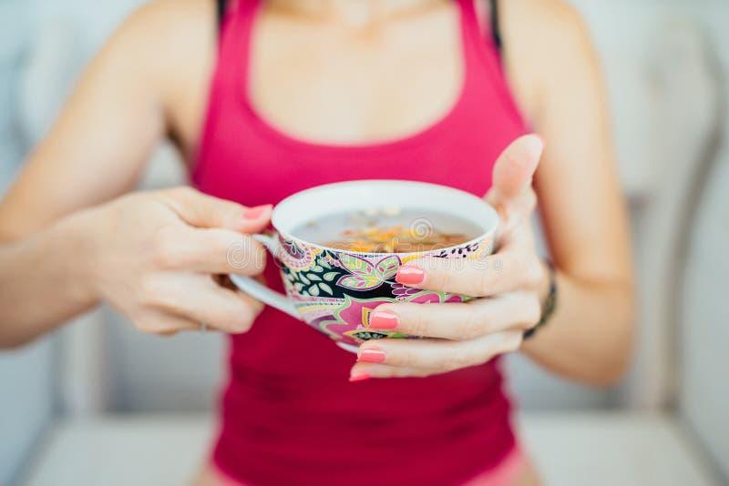 Las manos de las mujeres que sostienen una taza colorida de té imágenes de archivo libres de regalías