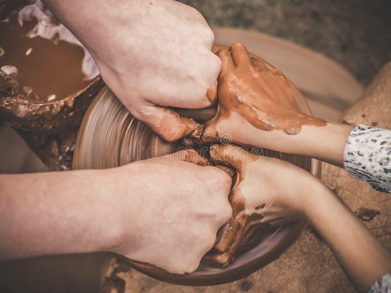 Las manos de los carftman de enseñanza de la cerámica A que dirigen una mano del niño, mostrando cómo lanzar un pote de arcilla e imagen de archivo