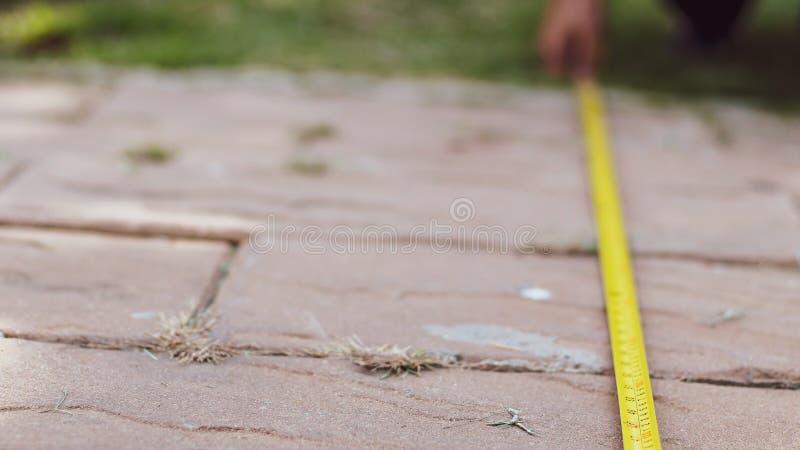 Las manos de los hombres detienen a una cinta métrica Construcci?n, ingenier?a, concepto de la reparaci?n fotos de archivo libres de regalías