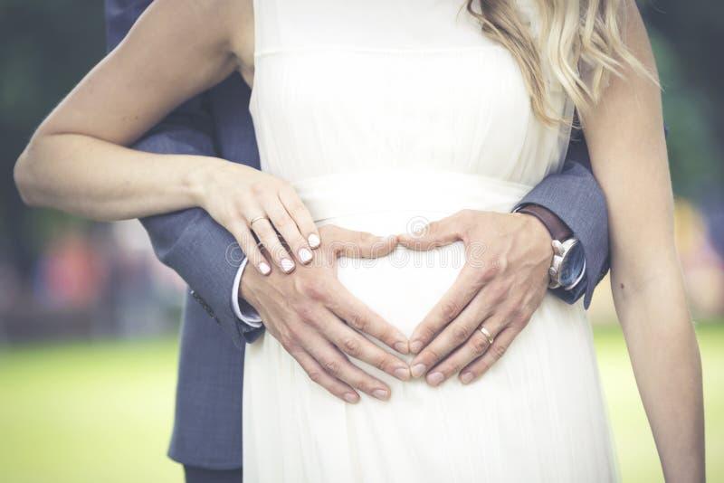 Las manos de los hombres en forma de corazón en el vientre de la mujer imagen de archivo