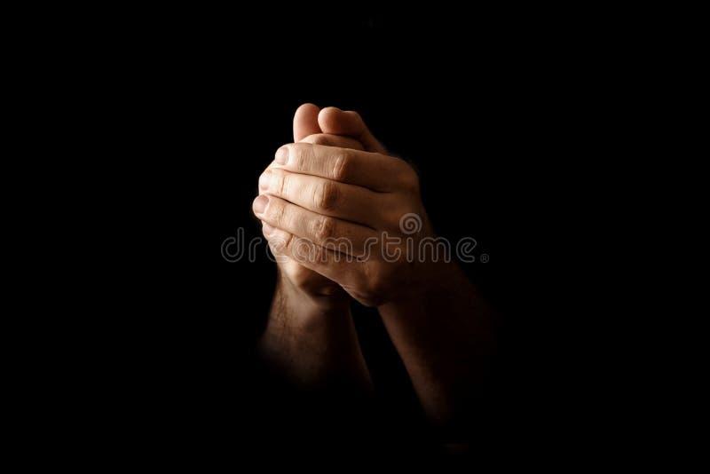 Las manos de los hombres en rezo en un fondo negro El concepto de fe, rezo, estando de luto, perdón, confesión foto de archivo libre de regalías