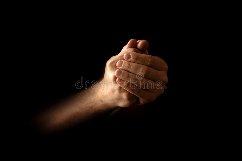 Las manos de los hombres en rezo en un fondo negro El concepto de fe, rezo, estando de luto, perdón, confesión fotografía de archivo