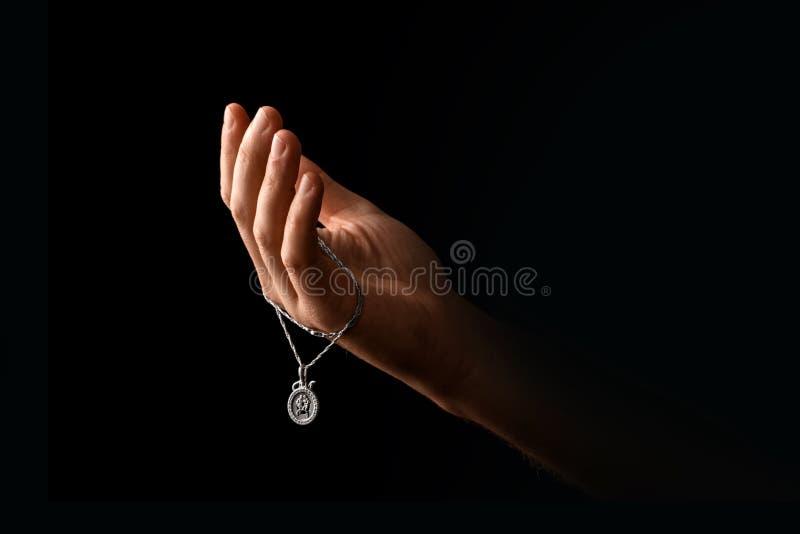Las manos de los hombres en rezo en un fondo negro El concepto de fe, rezo, estando de luto, perdón, confesión fotos de archivo libres de regalías