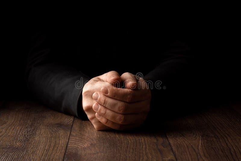 Las manos de los hombres en rezo en un fondo negro El concepto de fe, rezo, estando de luto, perdón, confesión fotos de archivo