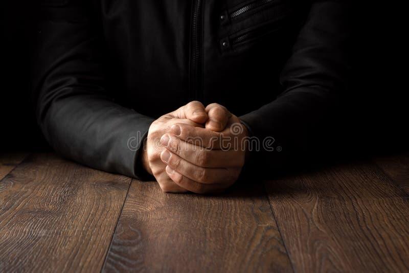 Las manos de los hombres en rezo en un fondo negro El concepto de fe, rezo, estando de luto, perdón, confesión imagen de archivo libre de regalías