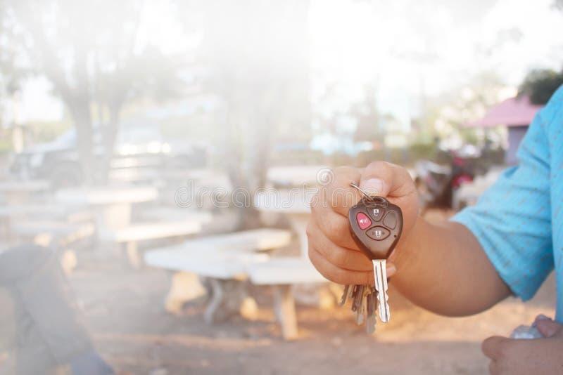 Las manos de los hombres están mostrando llaves del coche con desbloquear símbolos y alarmas foto de archivo libre de regalías