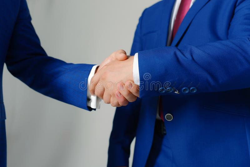 Las manos de los hombres de negocios en trajes formales se saludan Líderes de la compañía imagen de archivo libre de regalías