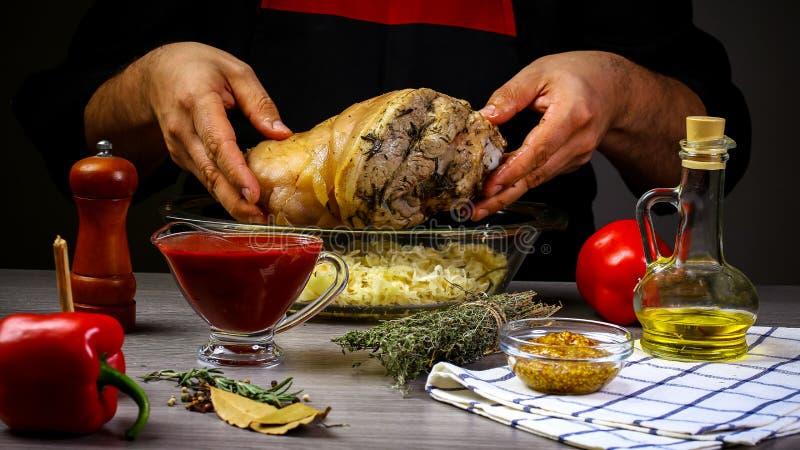 Las manos de los hombres, primer, sosteniendo el nudillo cortado del cerdo con la chucrut, cocinada para cocer Proceso de los pas foto de archivo