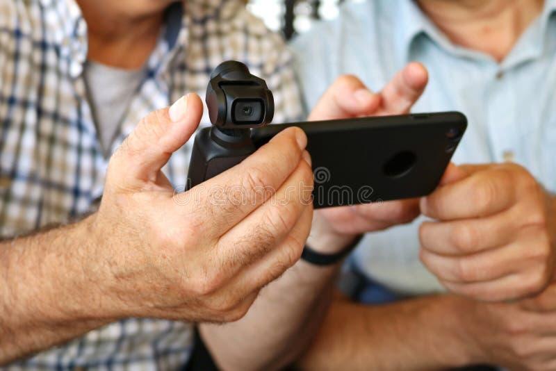Las manos de los hombres pusieron una nueva cámara y un teléfono móvil fotos de archivo libres de regalías