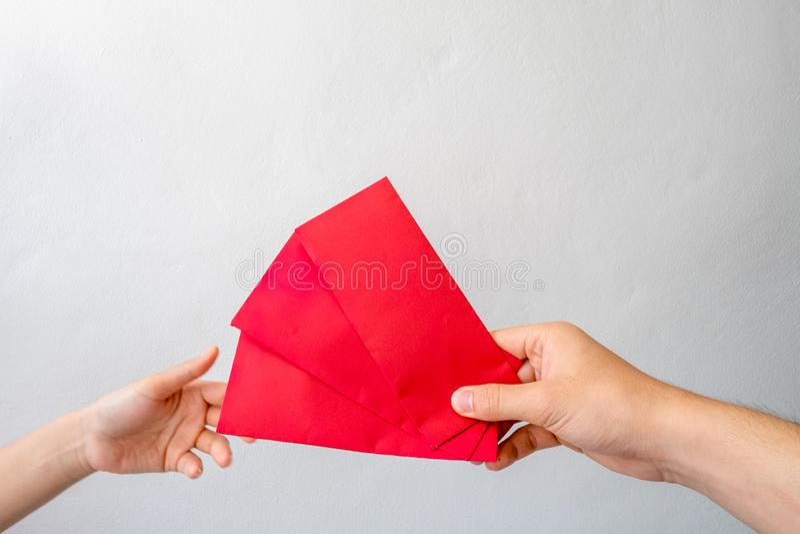Las manos de los hombres que sostienen el sobre de Angpang están representando la mujer joven para ser un regalo chino del día de imagen de archivo