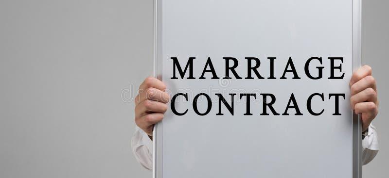 Las manos de los hombres que sostienen un cartel con el contrato de matrimonio de la inscripción aislado en fondo ligero fotografía de archivo