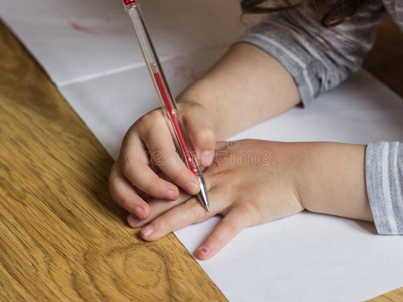 Las manos de los ni?os con el l?piz el ni?o dibuja en una hoja de papel fotografía de archivo