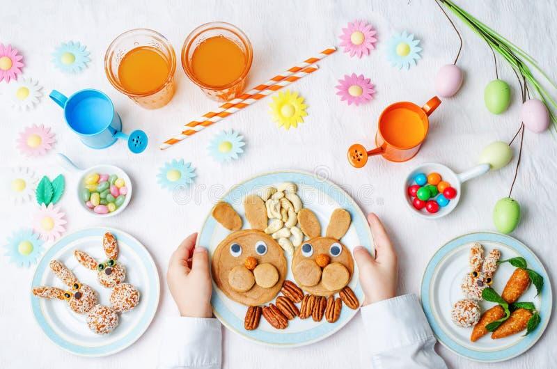 Las manos de los niños con las crepes, los dulces y el jugo para Pascua fotografía de archivo