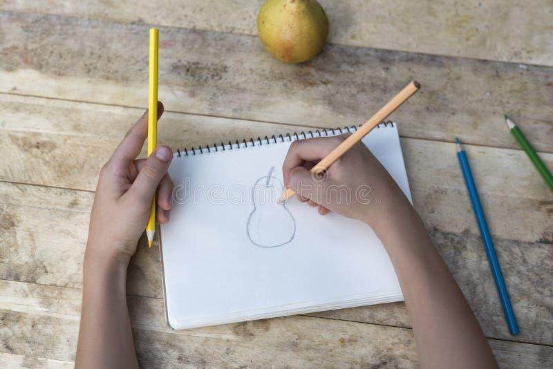 Las manos de los niños dibujan una pera con los lápices coloreados Visión superior imagen de archivo libre de regalías
