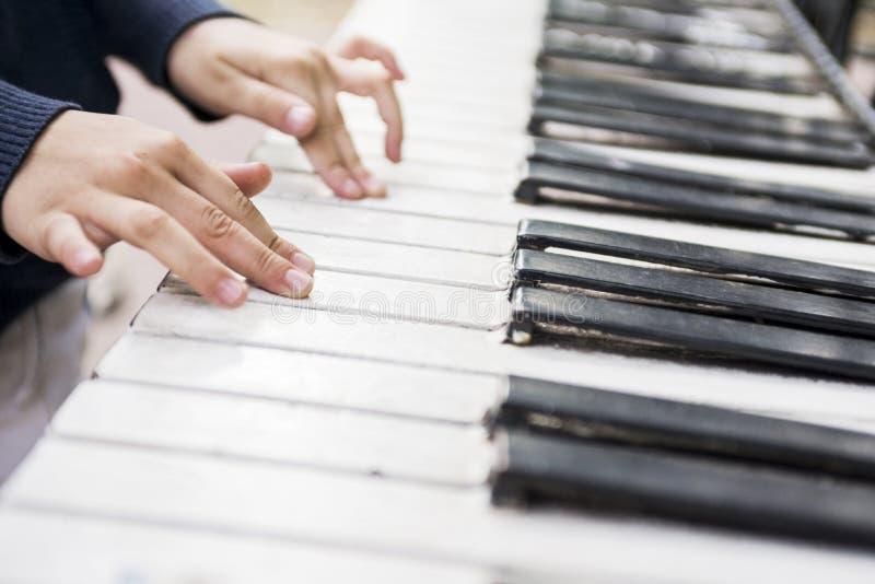 Las manos de los niños en las llaves del piano Lecciones de piano para los niños imagen de archivo libre de regalías