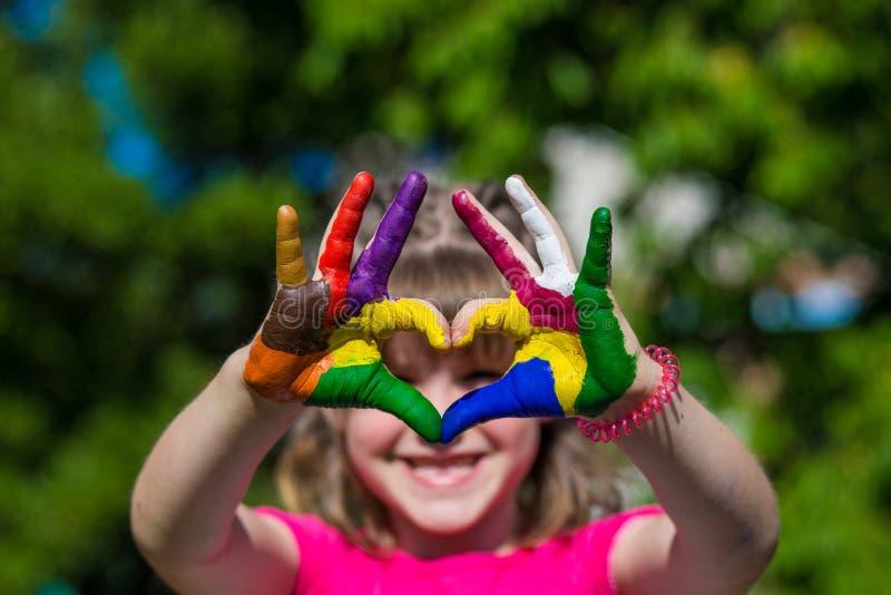 Las manos de los niños en pinturas del color hacen una forma del corazón, foco en las manos imagen de archivo