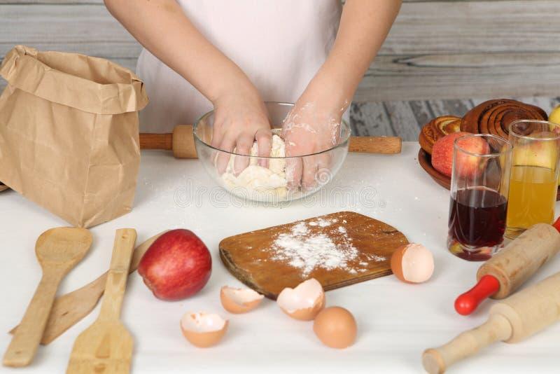 Las manos de los niños hacen la empanada fuera de los pasteles fotos de archivo