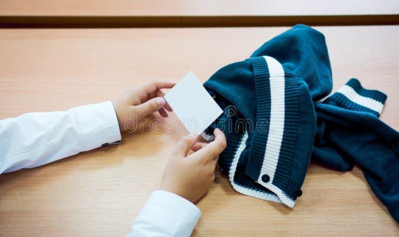 Las manos de los niños masculinos muestran una tarjeta de visita en blanco Estilo del tono del color del vintage del tiro del pri imágenes de archivo libres de regalías