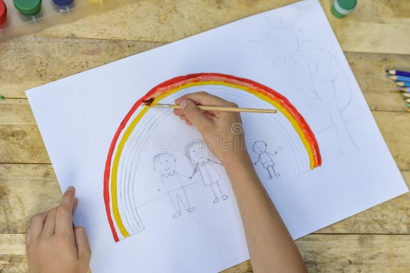 Las manos de los niños pintan un dibujo con un cepillo y las pinturas top VI foto de archivo libre de regalías