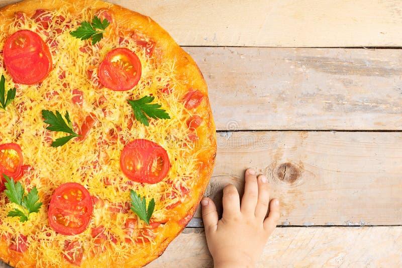 Las manos de los niños sostienen la pizza de queso con los tomates y la albahaca, comida en la tabla rústica de madera, visión su foto de archivo