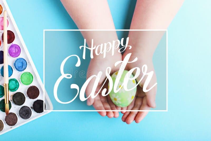 Las manos de los niños sostienen un huevo de Pascua hervido adornado, en un fondo azul imagen de archivo libre de regalías