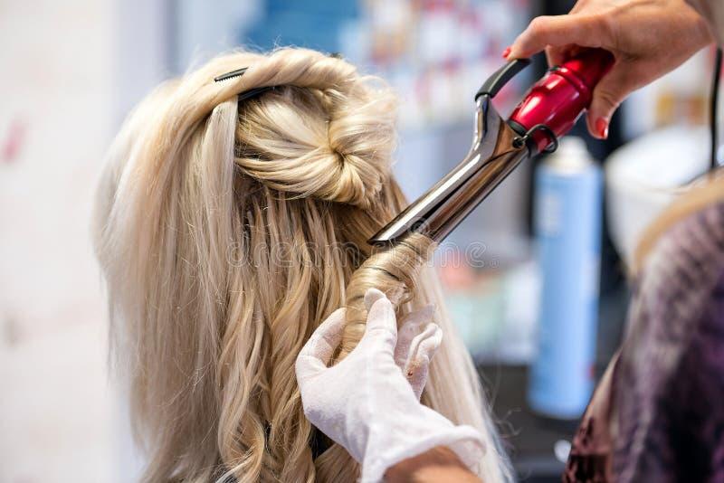 Las manos de los peluqueros con un círculo del pelo de las tijeras diseñaron al blonde imágenes de archivo libres de regalías