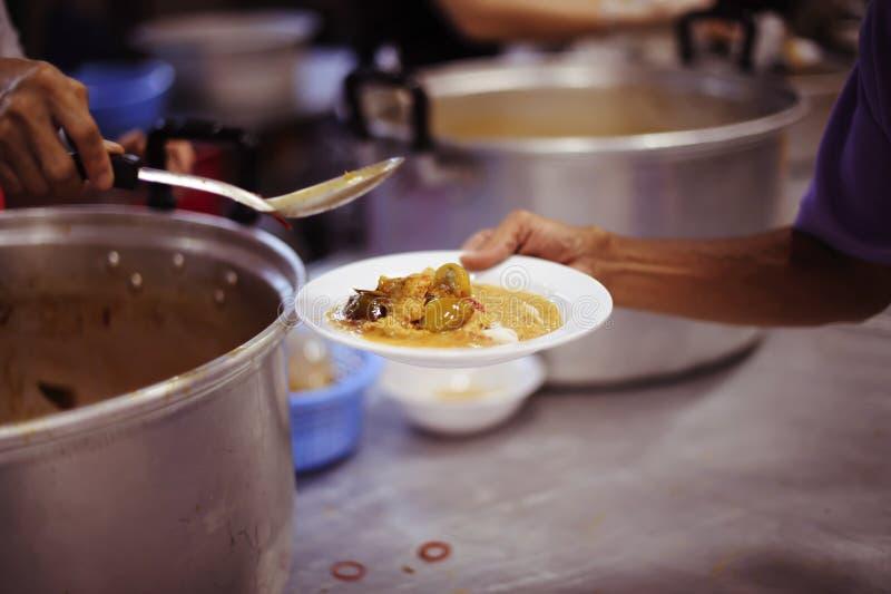 Las manos de los pobres están esperando donaciones de la comida para aliviar hambre: concepto de alimentación imágenes de archivo libres de regalías