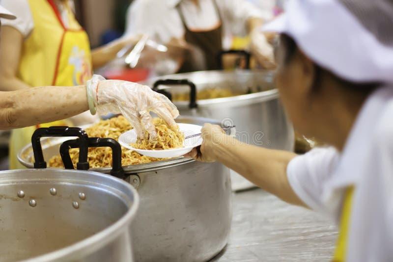 Las manos de los pobres están esperando donaciones de la comida para aliviar hambre: concepto de alimentación foto de archivo