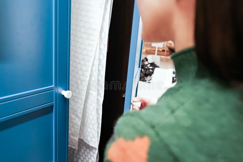 Las manos de las mujeres abren la puerta del armario/de gabinete, puerta de madera azul imagenes de archivo