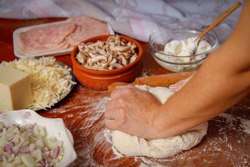 Las manos de las mujeres amasan la pasta para la pizza en la tabla de madera imagen de archivo
