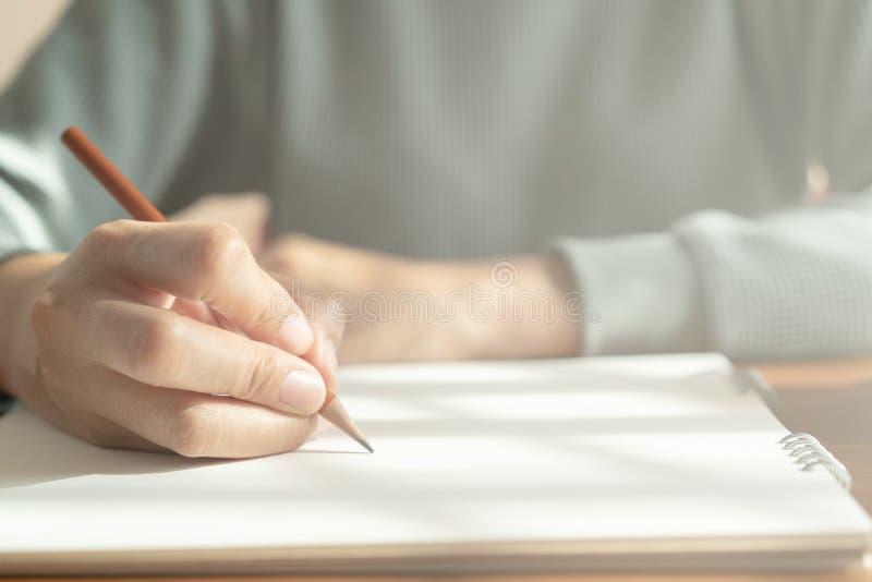 Las manos de mujeres asi?ticas est?n tomando notas sobre la tabla de madera fotos de archivo