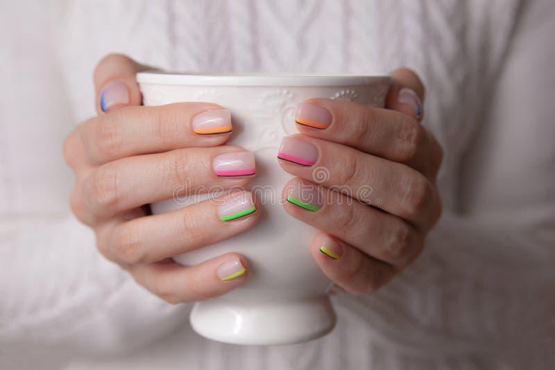 Las manos de las mujeres con una manicura hermosa del color y una taza de cerámica blanca fotos de archivo