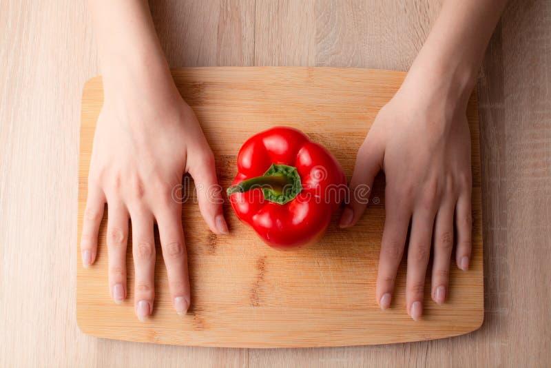 Las manos de las mujeres, cuchillo y un paprika en la tabla de cortar de madera foto de archivo