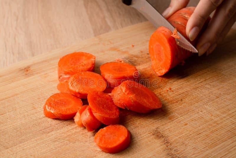 Las manos de las mujeres cuting una zanahoria en tabla de cortar de madera fotografía de archivo