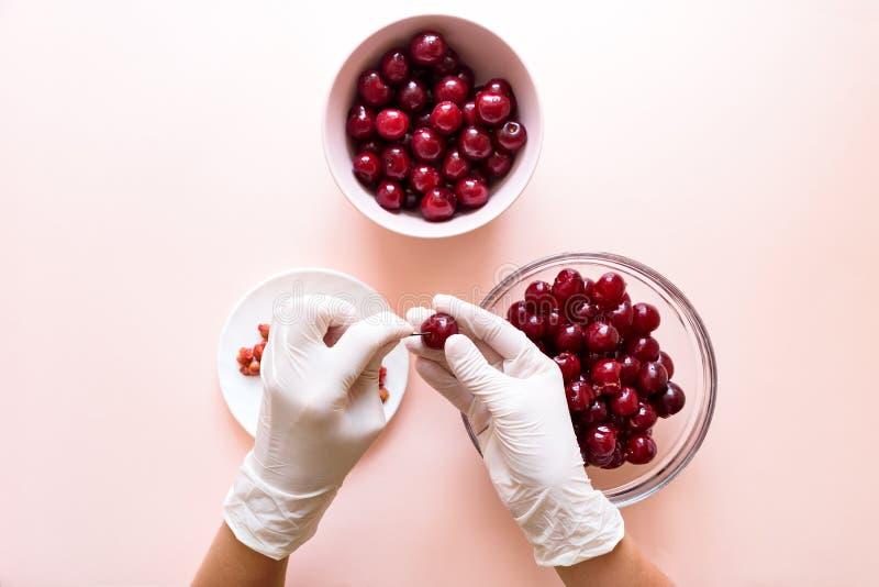Las manos de las mujeres en guantes quitan los huesos de la cereza con la horquilla Visi?n superior fotos de archivo