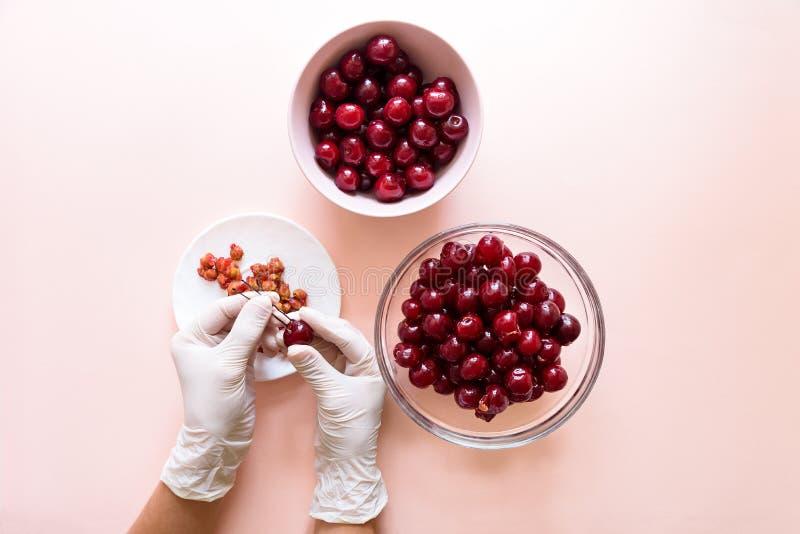 Las manos de las mujeres en guantes quitan los huesos de la cereza con la horquilla Visi?n superior fotos de archivo libres de regalías