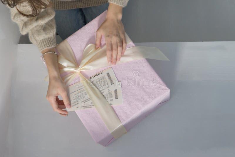 Las manos de las mujeres en una mentira ligera del suéter en una caja de regalo rosada grande hermosa, envuelta en una cinta beig foto de archivo