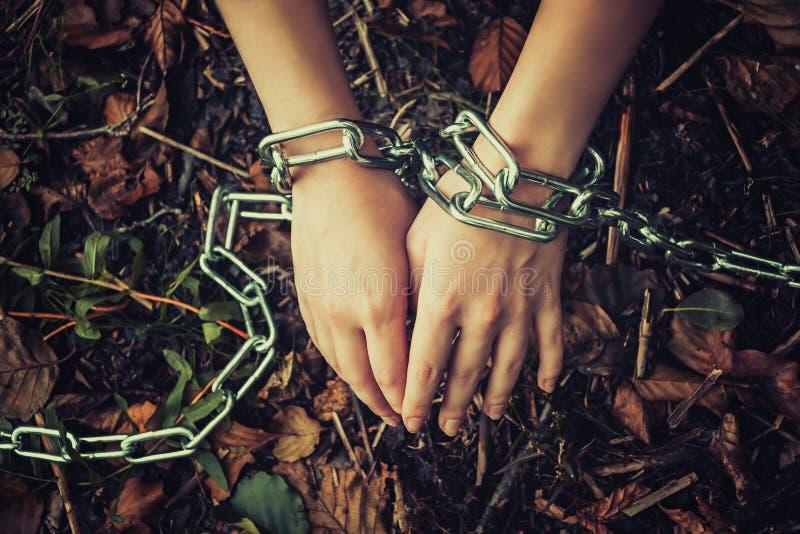 Las manos de las mujeres encadenaron en un bosque oscuro - el concepto de violencia, rehén, esclavitud imagenes de archivo